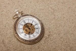 11105635-orologio-da-tasca-vecchio-sepolto-nella-sabbia-concetto-di-tempo-perso